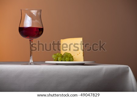 piece of cheese,a bunch of grapes and red wine - stock photo
