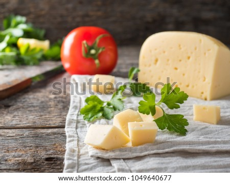 piece of cheese with parsley, tomatoes on a linen towel Rustic wooden background.