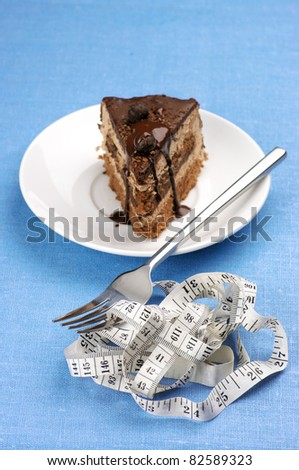 Piece of chocolate cake and measuring tape wrapped around fork on blue background.