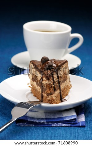 Piece of chocolate cake in white plate and white cup of coffee on blue background. - stock photo