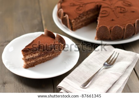 Piece of chocolate cake on a wooden table with the whole cake in the background