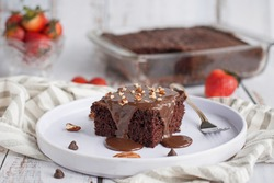 Piece of chocolate cake with chocolate pudding and pecans on top. The rest of the cake is in the background, along with some strawberries.