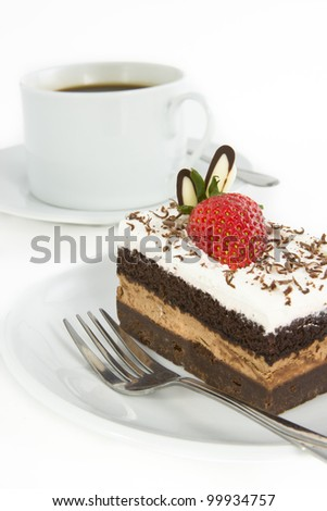 Piece of chocolate cake with strawberry decorate on top and cup of coffee