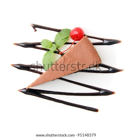 piece of chocolate cheesecake with mint twig and cherry on white background. Top view.