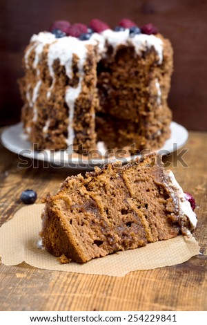 Piece of chocolate gingerbread cake on parchment paper on rustic wooden table, vertical close up image