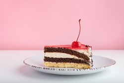 Piece of chocolate vanilla cake with maraschino cherry. Side view cake on white plate on pink background