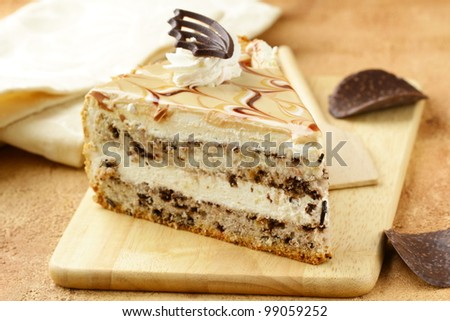 piece of cream  caramel cake with chocolate on a wooden board