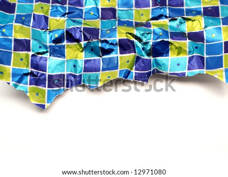 Piece of crumpled torn used wrapping paper over a white background
