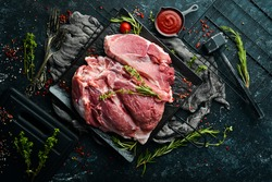 Piece of fresh raw pork from the neck, with ingredients and spices on a kitchen background. Meat. Top view. Rustic style.