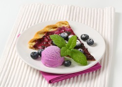 piece of fruit cake with fresh blueberries and ice cream