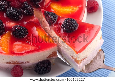 Piece of fruit yogurt cake. Cream and yogurt based fruit filling topped with jelly. Raspberries, blackberries, stawberries, and oranges.