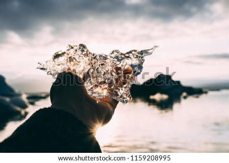 Piece of glacial ice holding in hand palm fingers iceberg water and sunset sky rays on the background #1159208995