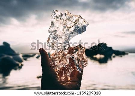 Piece of glacial ice holding in hand palm fingers iceberg water and sunset sky rays on the background #1159209010