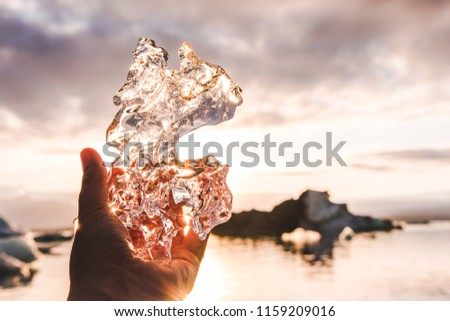 Piece of glacial ice holding in hand palm fingers iceberg water and sunset sky rays on the background #1159209016