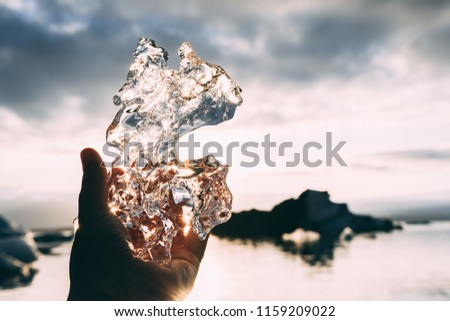 Piece of glacial ice holding in hand palm fingers iceberg water and sunset sky rays on the background #1159209022