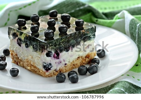 Piece of home made cheesecake with blueberries and green jelly