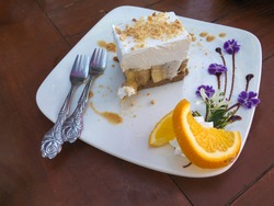 Piece of homemade banoffee cake with cream, banana, violet flower and slice orange decoration on white plate.