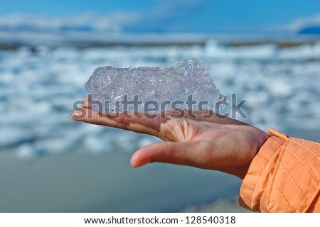 Piece of ice on woman hand. Jokulsarlon a lake in Iceland where icebergs collapsing from Vatnajokull glacier are floating around.