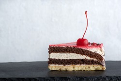Piece of layered chocolate cake garnished with cherries. Side view to piece of cake on white background.