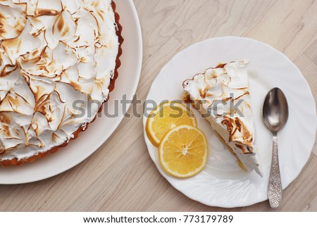 Piece of Lemon Meringue Pie on White Plate with Lemon Sliced on Wooden background