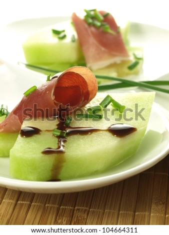 Piece of melon, rolled parma ham and balsamic vinegar