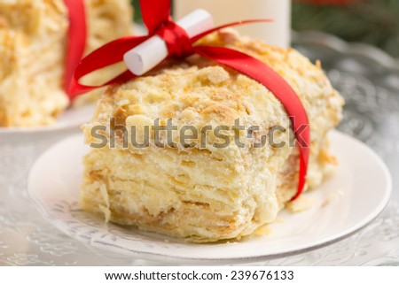 Piece of Napoleon cake for Christmas with red ribbon, candle and small scroll with Christmas wishes, close up