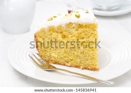 piece of orange cake decorated with Greek yogurt, honey and pistachios