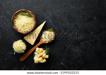 Piece of Parmesan cheese and cheese knife. On a stone background. Traditional Italian cheese. Top view. Free space for your text.