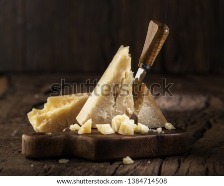 Piece of Parmesan cheese and cheese knife on the wooden board. Dark background. Foto d'archivio ©