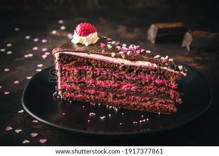 Piece of raspberry chocolate torte on a black plate on dark brown background Zdjęcia stock ©