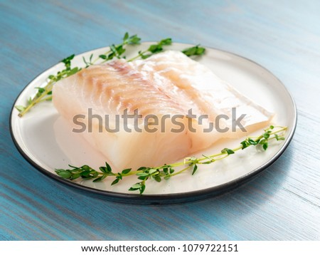 piece of raw cod fish fillet on plate on blue wooden table, side view
