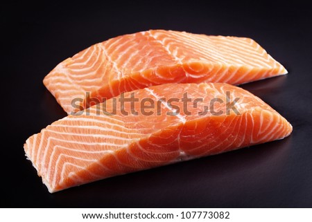 Piece of raw fresh salmon isolated on black background