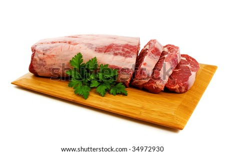 Piece of Raw Scotch Fillet partly cut into steaks.