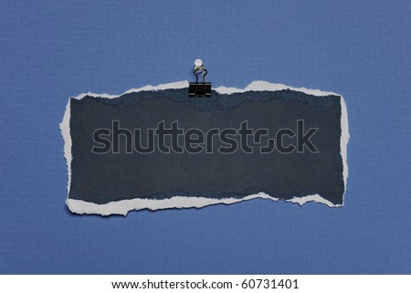 Piece of Rip Paper with white edges on a clip against a blue background