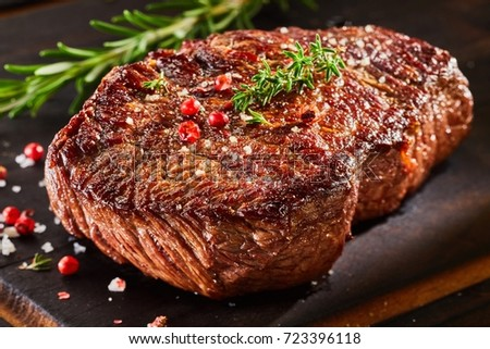 Piece of roast beef with spices served on wooden cutting board