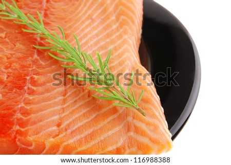 piece of salmon fillet on black plate over white and rosemary