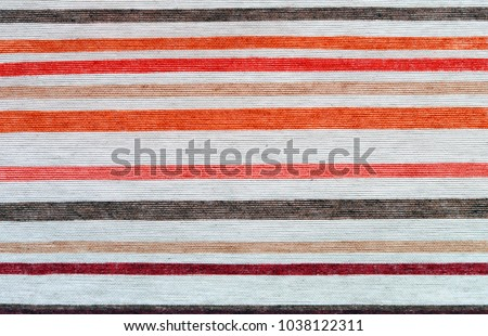 Piece of striped cloth. Traditional red white, orange and grey cotton fabric.  Classic rustic country home cooking design element for banner, border or background. Kithen style. #1038122311