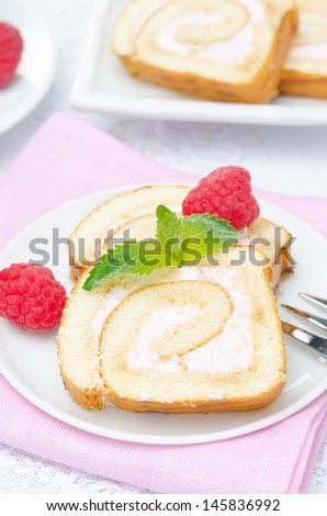 piece of swiss roll with raspberry cream on the plate, vertical, close-up