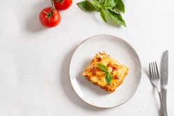 Piece of tasty hot lasagna served with a basil leaf on a gray plate. Italian cuisine, menu, recipe. Homemade meat lasagna. Copy space for text, top view