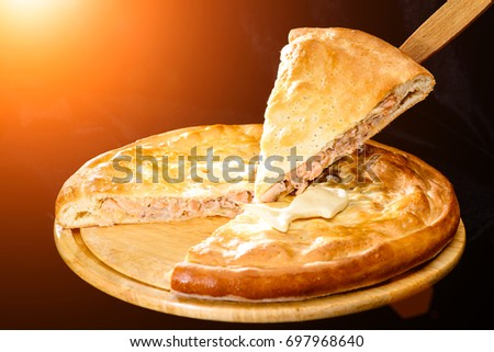 piece of tasty pie, round homemade delicious fish pie on wooden board in rays of the sun, dark background