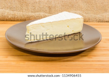 Piece of the brie cheese in the form of a sector on the brown dish on a wooden surface close-up at selective focus