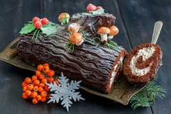 Piece of the traditional Christmas cake, snowflake and red berries on a wooden table.