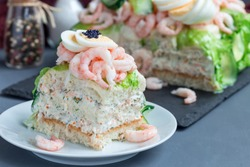 Piece of traditional savory swedish sandwich cake Smorgastorta with bread, shrimps, eggs, caviar, dill, mayonnaise, cucumber and lettuce, horizontal, closeup