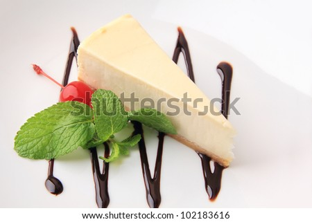piece of vanilla cheesecake with cherry and mint petal on a white background