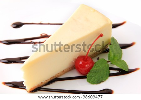 piece of vanilla cheesecake with cherry and mint petal on a white background - stock photo