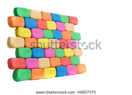 Piece of wall in perspective made of colorful plasticine bricks with copyspace
