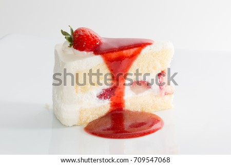 Piece of white cream strawberry cake with sliced strawberry stuff in middle, decorated with strawberry jam or sauce, moist smooth cake on white plate background, concept of cake or sweet dessert lover