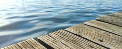 piece of wooden pier and waves in the sea