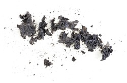 Pieces of burnt paper on a white background. The ashes of the paper.