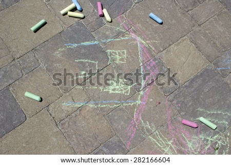 Pieces of colorful chalk and art drawn on cement pavers by a child